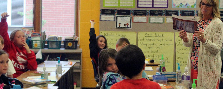 third grade teacher reading to class