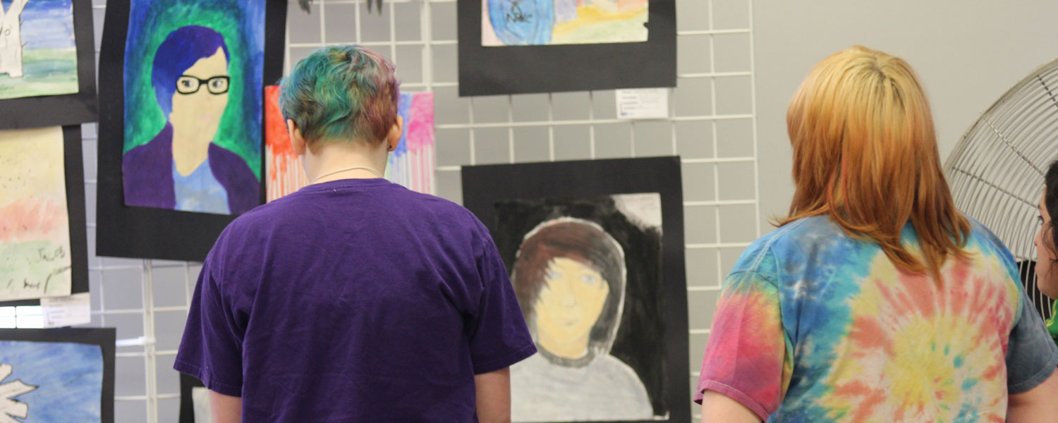 two students looking at student paintings