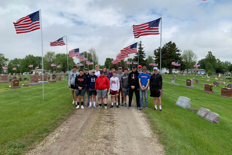 Members of Baseball Team Help Place Flags for Memorial Day